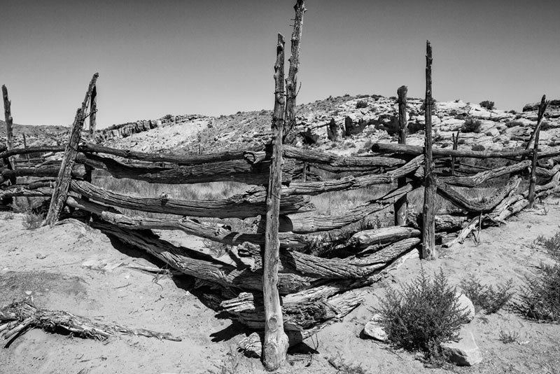 Black and white landscape photograph of an abandoned wooden horse corral in the Utah desert.