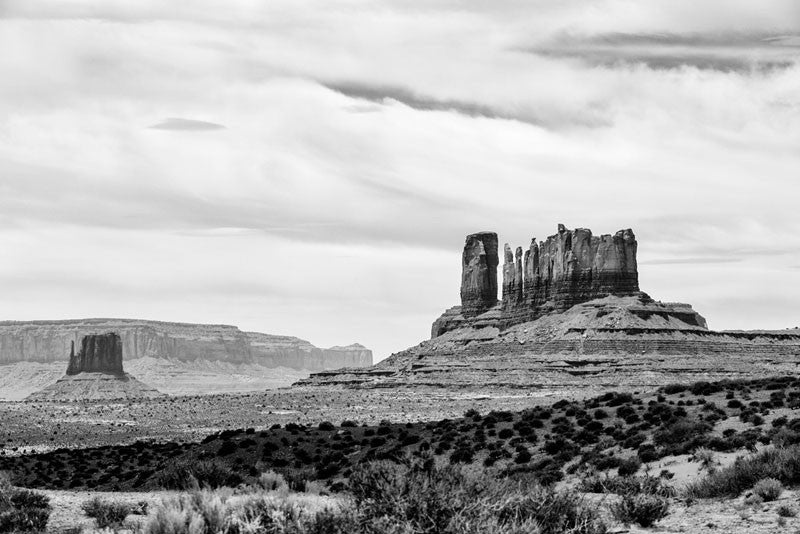 Black and white landscape photograph of giant stone mesas and buttes in Monument Valley, Utah.