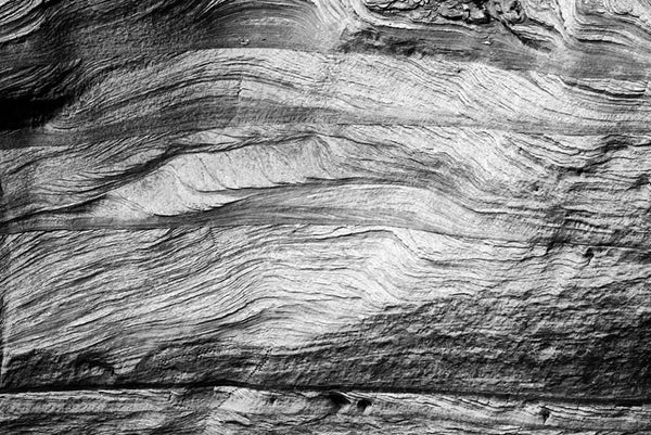 Black and white landscape photograph of natural stone textures along the walls of Canyon de Chelly in Arizona.