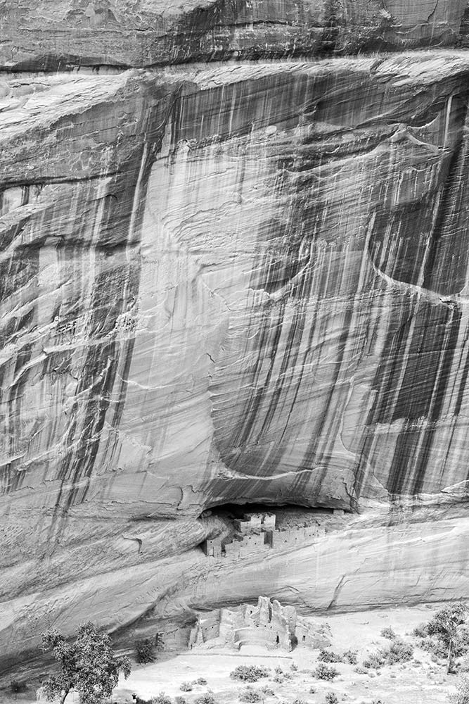 Black and white landscape photograph of the ancient ancestral Puebloan ruins known as the White House ruins in the floor of Canyon de Chelly in Arizona.