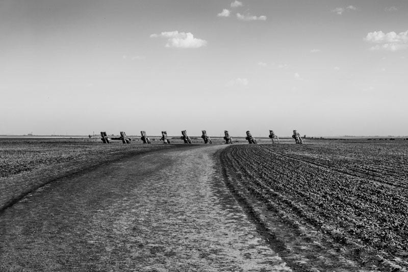 "Black and white landscape photograph of the flat Texas landscape around the famous public art piece ""Cadillac Ranch,"" in Amarillo, Texas."