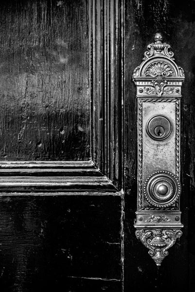 Black and white photograph of a black door with ornate brass knob and faceplate found