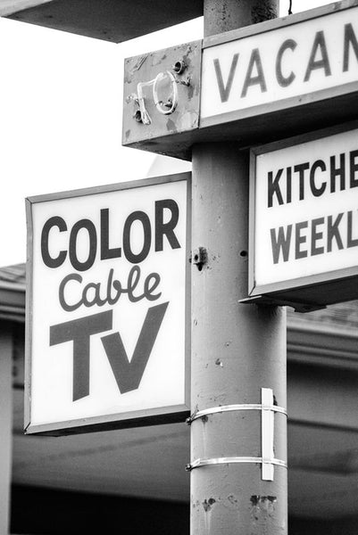 "Black and white photograph of an old 60s style roadside motel sign for a motel that has since been demolished. The signs promise amenities like ""Color Cable TV,"" and ""Kitchenettes,"" and ""Weekly Rates."""