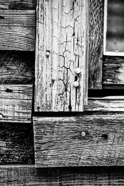 Black and white photograph of weathered boards on the exterior of the home of late blues musician Sleepy John Estes in Brownsville, Tennessee.