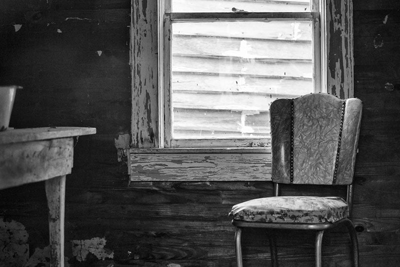 Black and white photograph of an old wooden table and a chair inside the home of the late blues musician Sleepy John Estes in Brownsville, Tennessee. The small shack where Estes lived has been preserved and relocated to a visitors center near the schoolhouse of Tina Turner, who also hails from Brownsville. The wall of Turner's school is visible through the window.