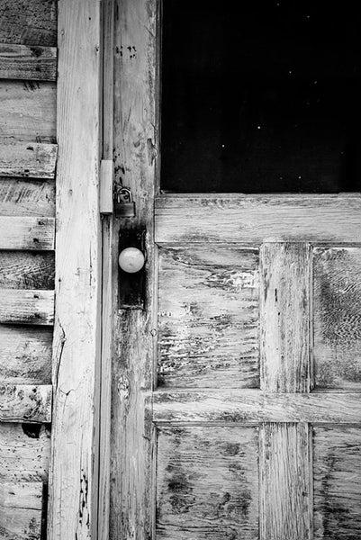 Black and white photograph of weathered and textured front door to the home of late blues musician Sleepy John Estes in Brownsville, Tennessee.