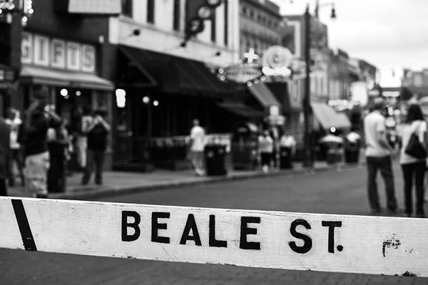 Black and white photograph of Memphis famous entertainment district on Beale Street, with the street name spray-painted on a street barricade.