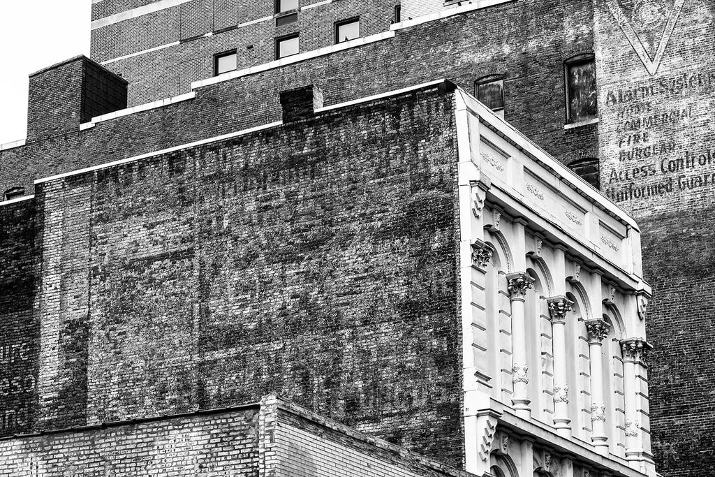 Black and white photograph of layers of antique fading advertising signs on the sides of the old Climax and Utopia Hotel buildings in downtown Nashville.