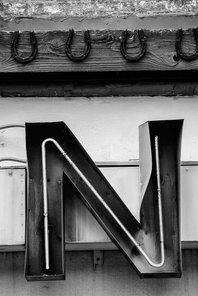 Black and white photograph of a dented red neon letter N with a row of lucky horseshoes nailed above it, spotted on Lower Broadway in Nashville, Tennessee.