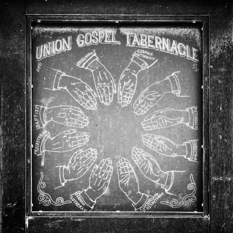 "Black and white photograph of an old sign for the  Union Gospel Tabernacle — which later became the world-famous Ryman Auditorium — in Nashville. Its origins as a church and its clearly non-secular architecture led to the Ryman's nickname, ""The  Mother Church of Country Music."""