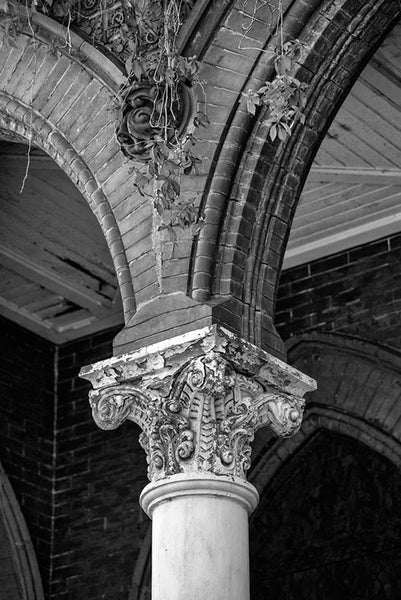 Black and white photograph of Louisville's abandoned Quinn Chapel, a historic church falling into ruin but still quite beautiful and evocative with it's peeling, white columns, arches, and creeping ivy.