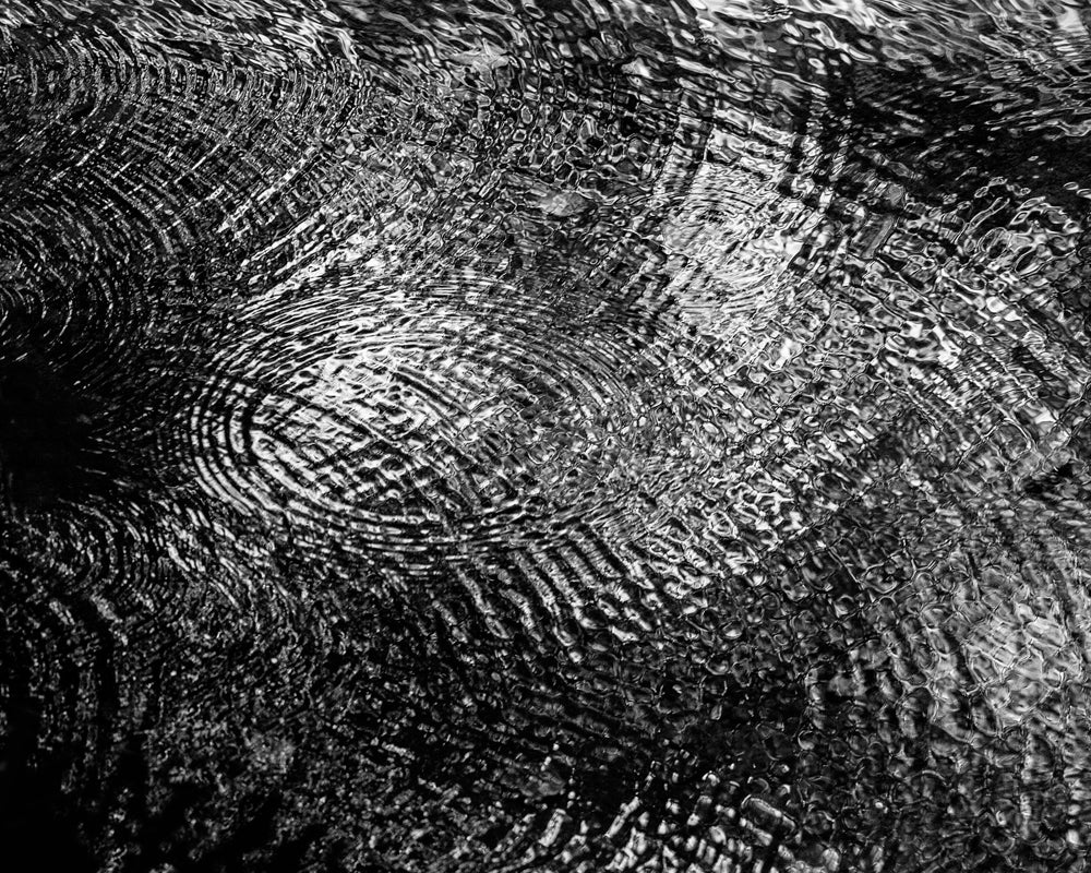 Black and white photograph of a complex, overlapping array of river ripples cropped to make an abstraction from nature.