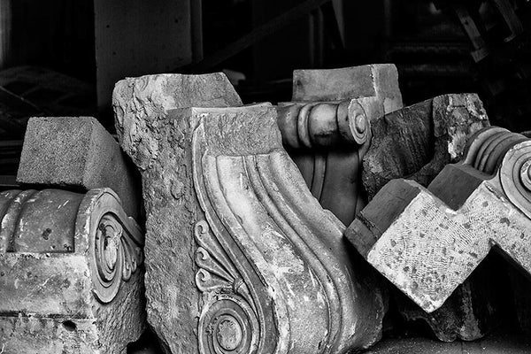 Black and white photograph of a grouping of architectural elements stored in an empty storefront while a building undergoes renovation in downtown Memphis.