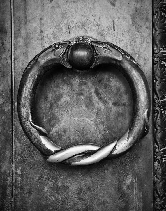 Black and white photograph of the ring of serpents door handles on the huge brass doors at Nashville's Parthenon. Nashville is home to a full-size replica of the Athenian Parthenon, complete with a magnificent 42-foot statue of Athena Parthenos by artist Alan LeQuire. These brass rings can be seen on the exterior doors, which are 24 feet tall, one foot thick, and way 7.5 tons each.