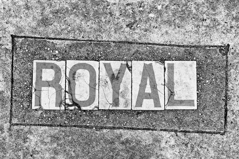 "Black and white fine art photograph of the word ""Royal"" in a sidewalk in the French Quarter of New Orleans, Louisiana."