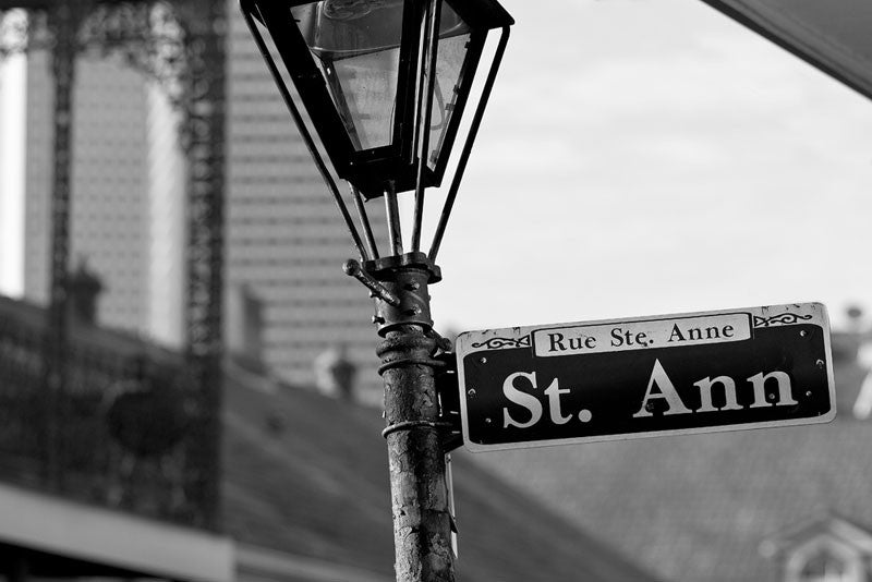 Black and white photograph of a street sign for Rue St. Anne (St. Ann Street) in the New Orleans' French Quarter.