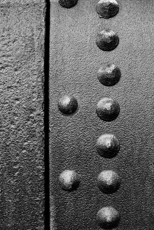 Black and white industrial detail photograph of rusty rivets on a curved sheet of rusty metal, part of an antique machine.