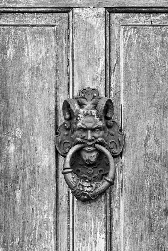 Black and white photograph of an ornate satyr door knocker on a house in the New Orleans' French Quarter.
