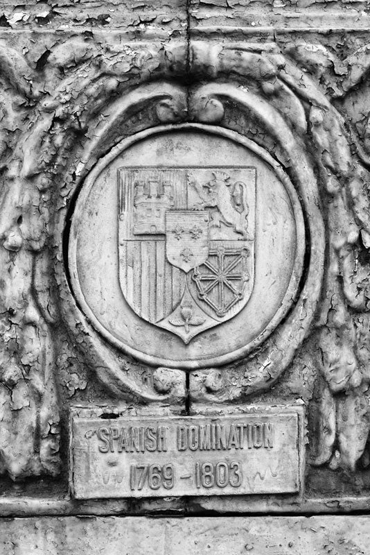 "Black and white photograph of an ornate street pole crest, part of a series illustrating the nations that have ruled over Louisiana in the past, seen along Basin Street in New Orleans. The metallic sign says, ""Spanish Domination 1769 - 1803."""