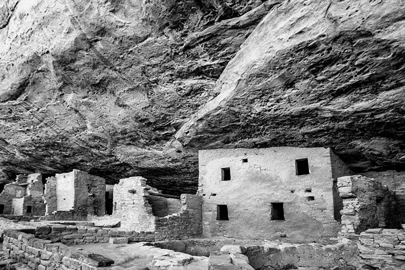 Black and white fine art photograph of Spruce Tree House, seen in its sheltered location under the overhanging edge of Mesa Verde in Colorado.
