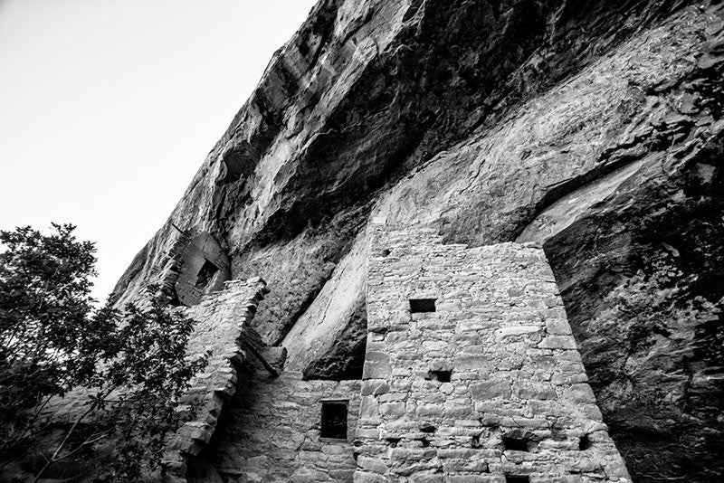 Black and white fine art photograph looking up at the tall vertical walls of Spruce Tree House, seen in its sheltered location under the overhanging edge of Mesa Verde in Colorado.