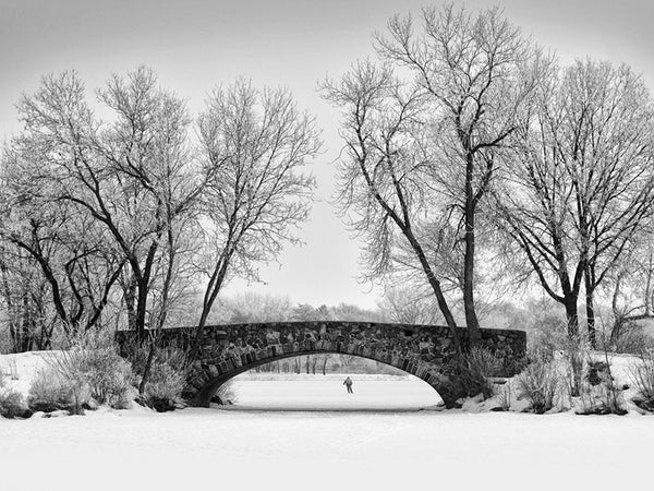 Black and white photograph of an ice skating pond with an old stone bridge arching over it. In the distance, the ice tester skates alone on the ice, ensuring that it's safe for the general public to skate.