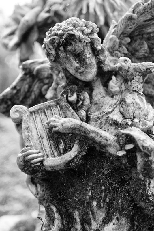 Black and white photograph of a small moss-covered cemetery angel in Savannah's famous, beautiful, and creepy Bonaventure Cemetery.