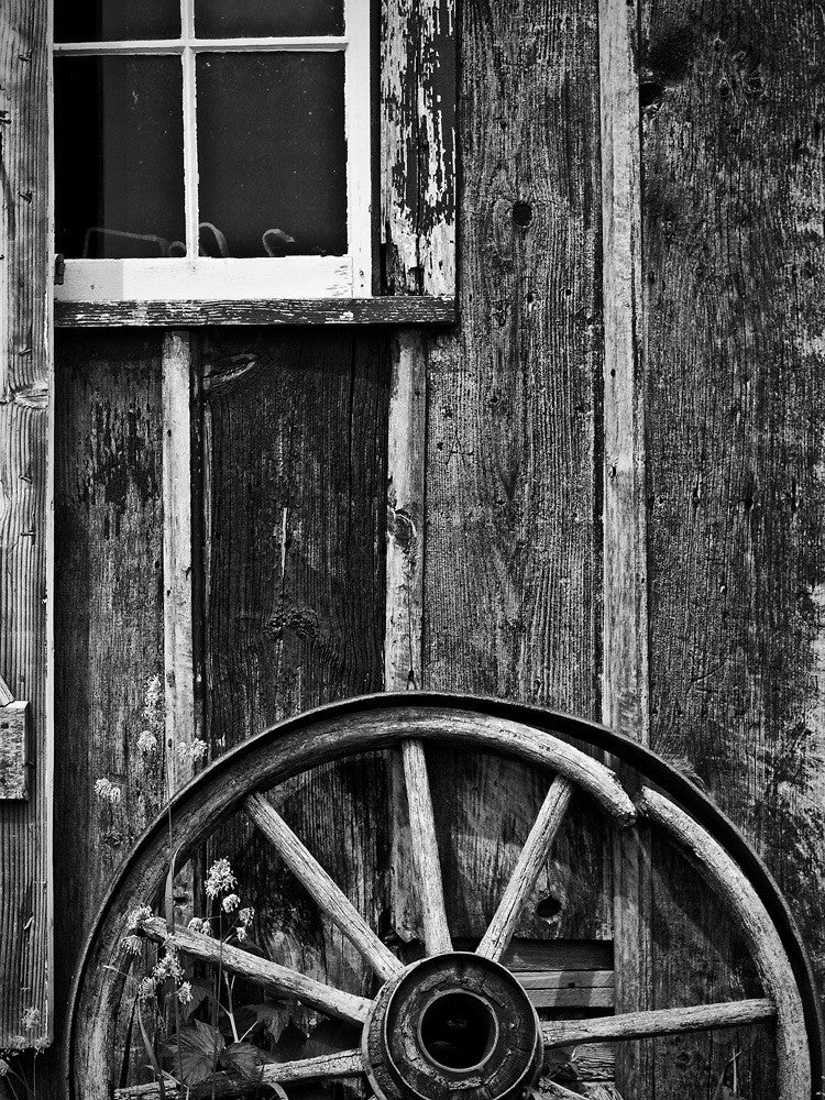 Black and white photograph of a broken wagon wheel leaned against the side of a textured wooden workshop.