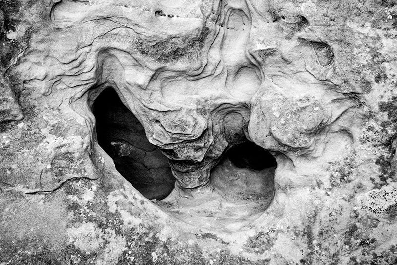 Black and white fine art photograph of an interesting stone formation in a rock wall face along the hiking trail at Mesa Verde, Colorado.