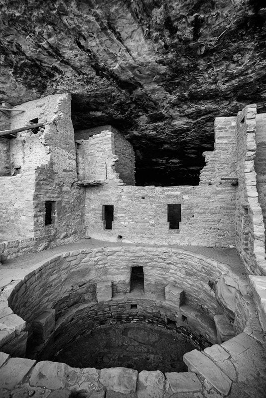 Black and white fine art photograph of ancient rooms and an open kiva at Mesa Verde, Colorado. The blackened streaks on the ceilings are the carbon remains of smoke from ancient cooking fires.