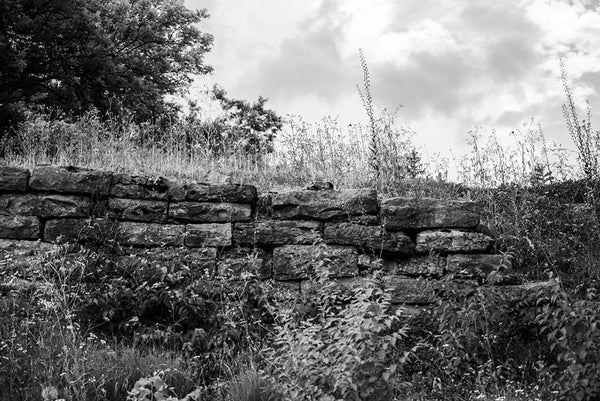Black and white photograph of the old stone ruins of Fort Negley on a hillside near Nashville. Fort Negley is a star-shaped structure built of limestone blocks on a hilltop south of the city, and was the largest inland fort built during the American Civil War. The fort was built by the Union army in 1862 as a defensive post after the Confederates lost control of Nashville in successive battles, but with fighting concentrated in other areas, the fort never saw action.