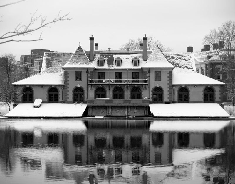 Black and white photograph of Harvard's Weld Boat House in winter, reflecting in the cold, black Charles River.