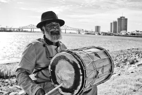 "Black and white fine art photograph of a New Orleans street musician on the levee playing a drum and singing ""When the saints go marching in."" In the background is the Greater New Orleans Bridge (aka Crescent City Connection) over the Mississippi River."