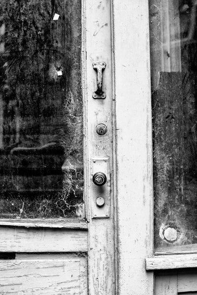 Black and white fine art photograph of a white door with cobwebs in the windows for an abandoned storefront in downtown Memphis, Tennessee.