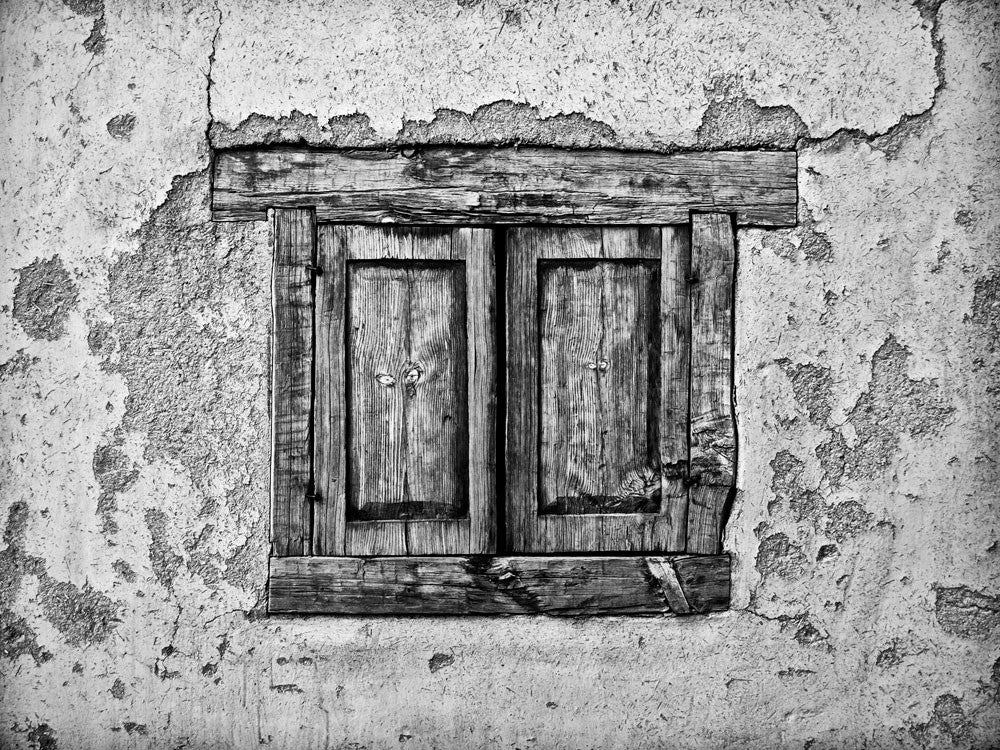 Black and white architectural detail  photograph of the textural adobe walls and shuttered window of an old house in Taos, New Mexico, where Kit Carson once lived.