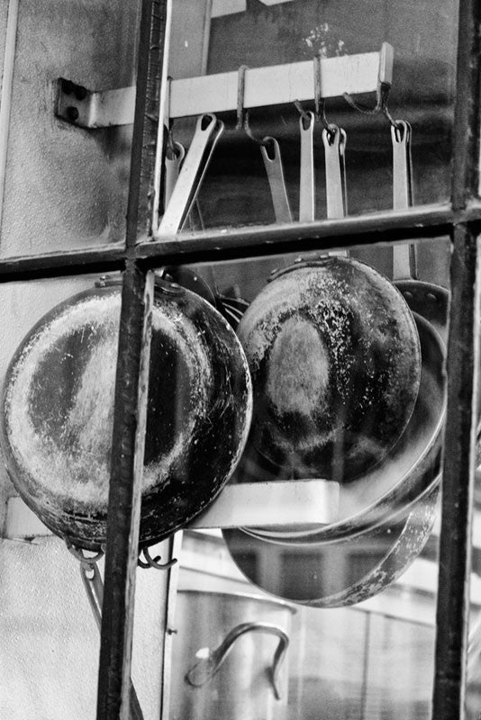Black and white fine art photograph of pots and pans hanging in the window of a French Quarter gourmet restaurant kitchen in New Orleans, Louisiana.