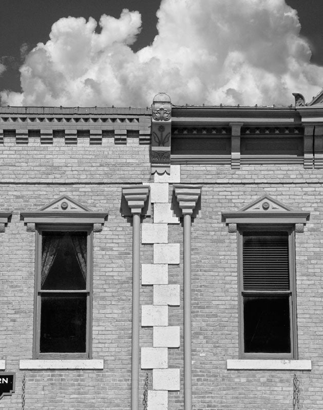 Black and white photograph of a historic architecture on the downtown courthouse square in Georgetown, Texas. The white stone work is reminiscent of a zipper running between two structures.