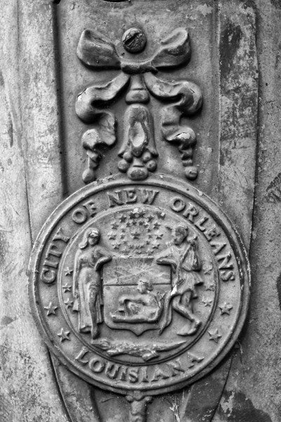 "Black and white photograph of an ornate ""City of New Orleans Louisiana"" street pole crest, seen along Basin Street in New Orleans."