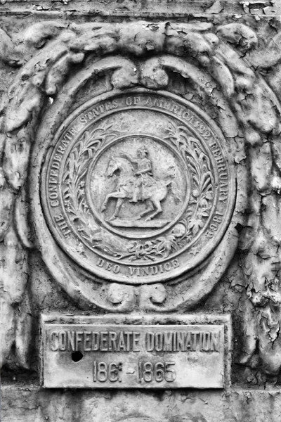 "Black and white photograph of an ornate street pole crest, part of a series illustrating the nations that have ruled over Louisiana in the past, seen along Basin Street in New Orleans. The metallic sign says, ""Confederate Domination 1861 - 1865."""