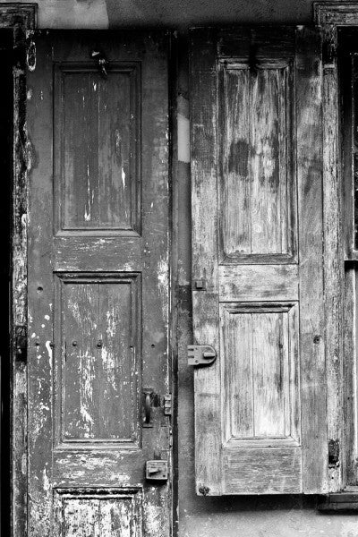 Black and white photograph of a weathered French-style wooden door and window shutter in the French Quarter of New Orleans.