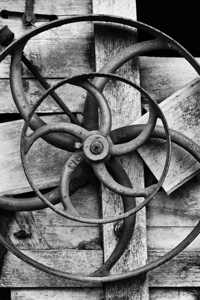 Black and white photograph of a piece of antique farm equipment featuring wheels inside of wheels.