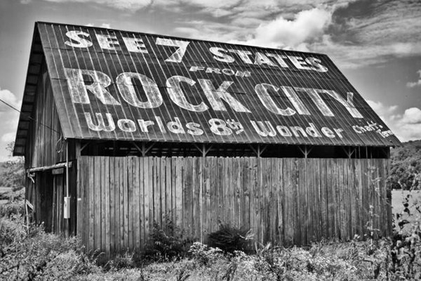 Black and white photograph of a rural barn featuring the famous and historic See Rock City ad painted on its tin roof.