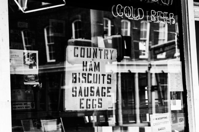 Black and white fine art photograph of store window on Front Street in downtown Memphis. The homemade sign offers Country Ham, Biscuits, Sausage, Eggs, and also Cold Beer.