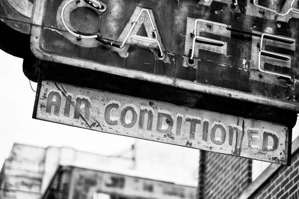 Black and white photograph of a fading, vintage neon cafe sign on Beale Street in Memphis.