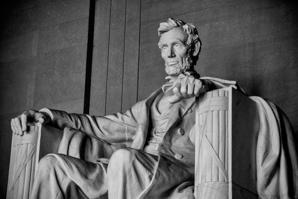 Black and white photograph of the huge statue of Abraham Lincoln at the Lincoln Memorial in Washington, D.C., seen from the right side in a three-quarter view.