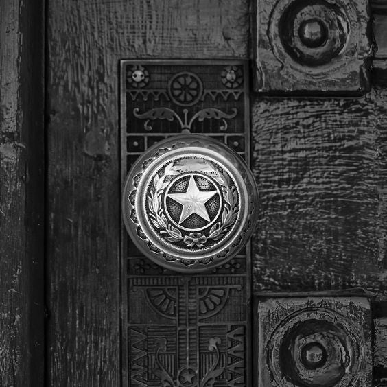 Black and white photograph of a brass lone star door knob on a door leading into the Texas State Capitol Building in Austin. (Square format)  This is one of the well-worn door knobs leading into the magnificent Texas state capitol building in Austin. Imagine how many interesting characters from Texas history must have touched this knob, and how many scoundrels!