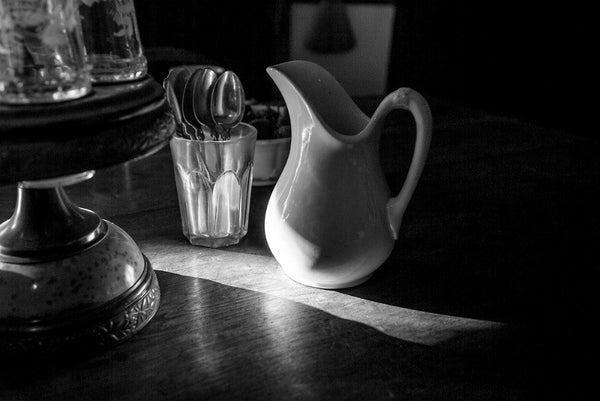 Black and white photograph of a shaft of morning sunshine shining over a dining table with a small cream pitcher in one of the 19th century houses at the historic South Union Shaker Village in Kentucky.