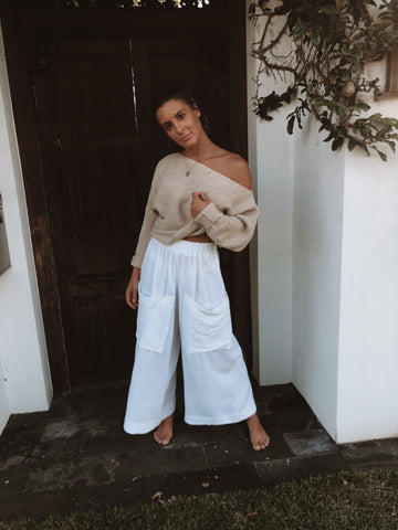 Girl in white pants an off the shoulder knit