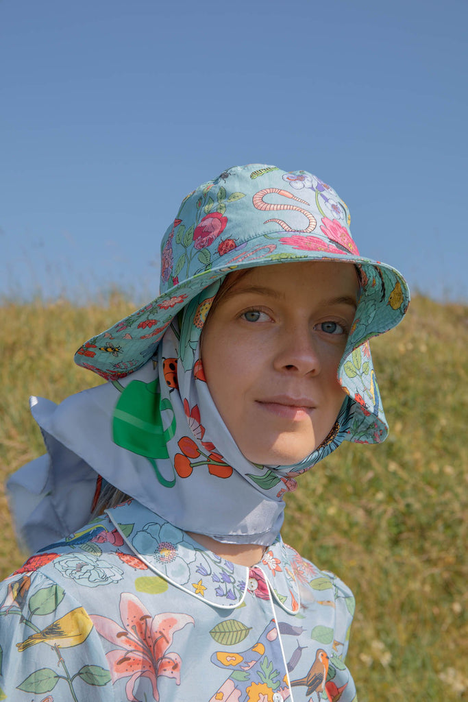 Garden Birds Sun Hat flowers, insects and birds. Shown here on a model, wearing the matching garden birds pale blue scarf and cotton pyjama shirt. Photographed on a sunny day.