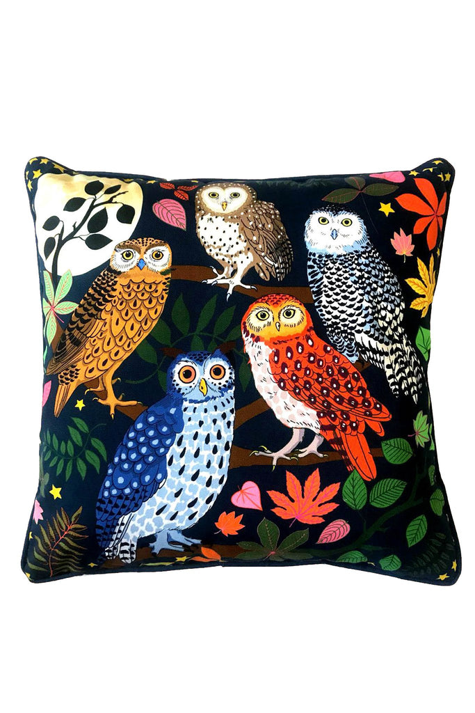 Karen Mabon Night Owl Cushion with dark background, featuring five owls in a mix of blue, red and brown. Standing on branches, with moonlight in the background.